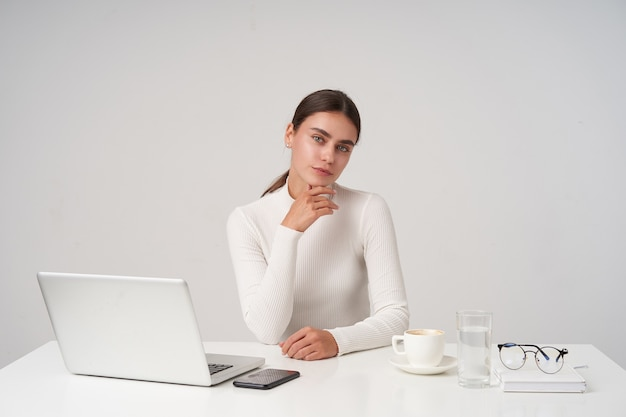 Positiva, jovem e encantadora senhora morena segurando o queixo com a mão levantada e sorrindo ligeiramente enquanto olha para a câmera, usando um decote de malha branca enquanto posava sobre uma parede branca
