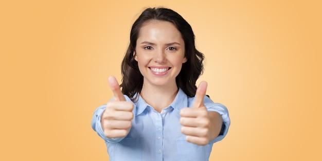 Positiva jovem expressando felicidade e mostrando ok