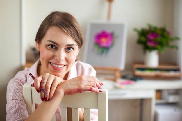 Positiva jovem linda sorridente garota artista trabalha em estúdio seleciona as cores da cama para o trabalho com flor de rosa mosqueta, sentado à mesa com um cavalete e um buquê. conceito de criatividade como profissão