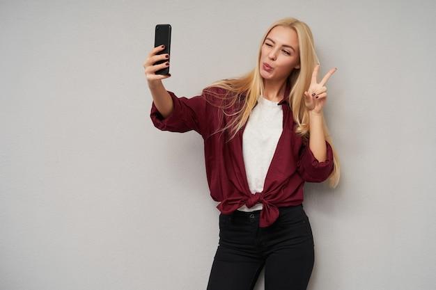 Positiva jovem loira de cabelos compridos segurando o smartphone e piscando para a câmera, levantando a mão com o sinal da vitória ao fazer selfie, posando sobre fundo cinza claro