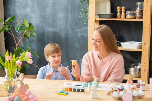 Positiva jovem mãe e filho fofo sentados à mesa na cozinha doméstica e fazendo desenhos engraçados de ovos na páscoa