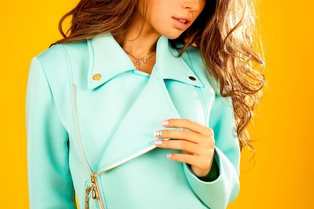 Positiva jovem modelo com cabelos ondulados na jaqueta.