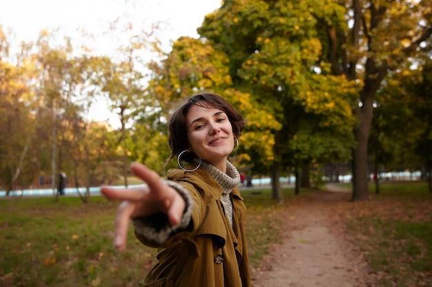 Positiva jovem morena atraente com penteado casual sorrindo agradavelmente e estendendo a mão levantada, caminhando sobre as árvores amareladas no parque da cidade