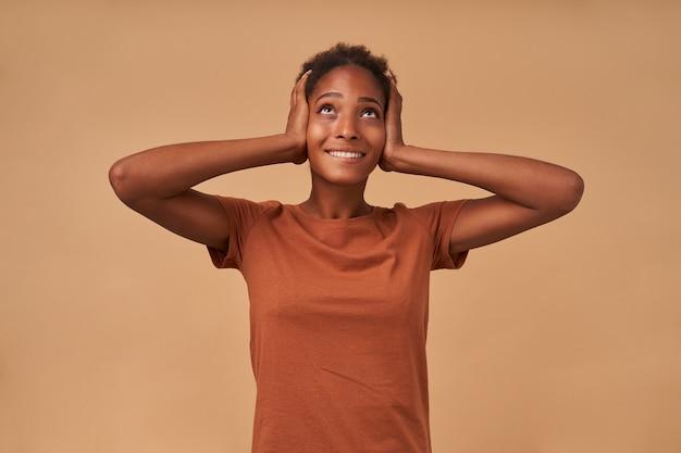 Positiva jovem morena encaracolada com penteado coque, levando as mãos às orelhas e sorrindo amplamente enquanto olha para cima, isolada em bege