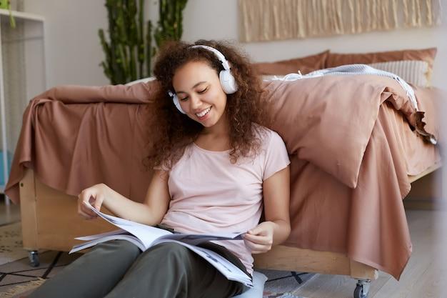 Positiva jovem mulher afro-americana com cabelos cacheados localização na sala, lendo a nova revista e curtindo sua música favorita em fones de ouvido, sorrindo e olhando.