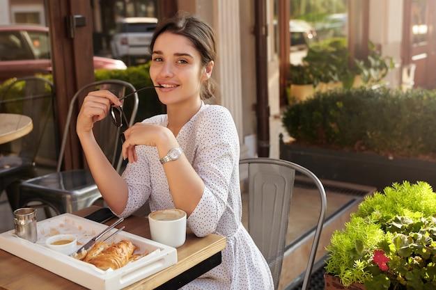 Positiva, jovem senhora de cabelos escuros de olhos castanhos, olhando com um sorriso encantador e segurando os óculos de sol na mão levantada, vestida com um vestido de bolinhas branco enquanto toma o café da manhã ao ar livre