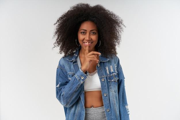 Positiva, jovem senhora de pele escura com cabelo encaracolado, vestindo roupas casuais sobre parede branca, com um sorriso alegre e segurando o dedo indicador nos lábios, pedindo para guardar segredo