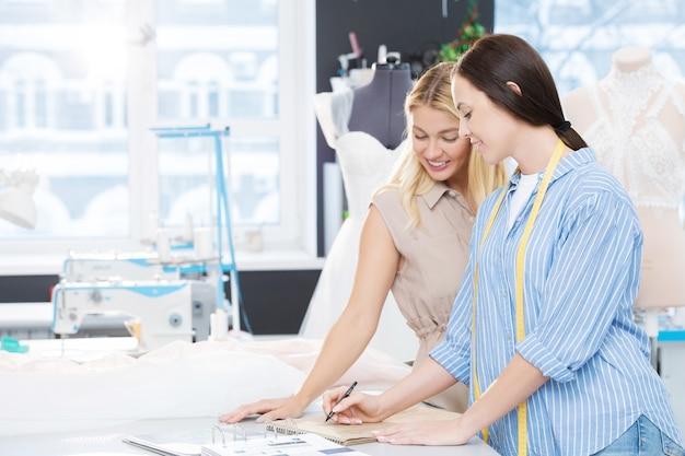 Positiva, linda jovem noiva criando vestido de noiva com designer em estúdio de costura