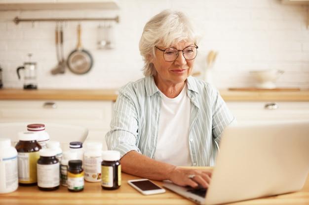 Positiva, linda mulher de cabelos grisalhos, aposentada em óculos, escolhendo estilo de vida saudável, sentada na cozinha com suplementos dietéticos, digitando no laptop, digitando resenha na loja online