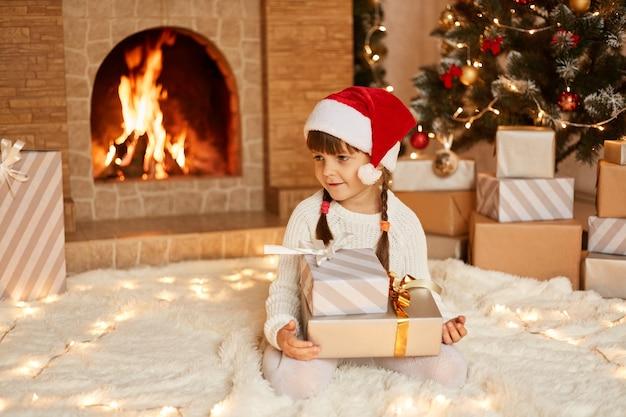 Positiva menina bonitinha vestindo suéter branco e chapéu de papai noel, segurando a pilha de presentes nas mãos, sentado no chão em um tapete macio perto da árvore de natal, caixas de presentes e lareira.