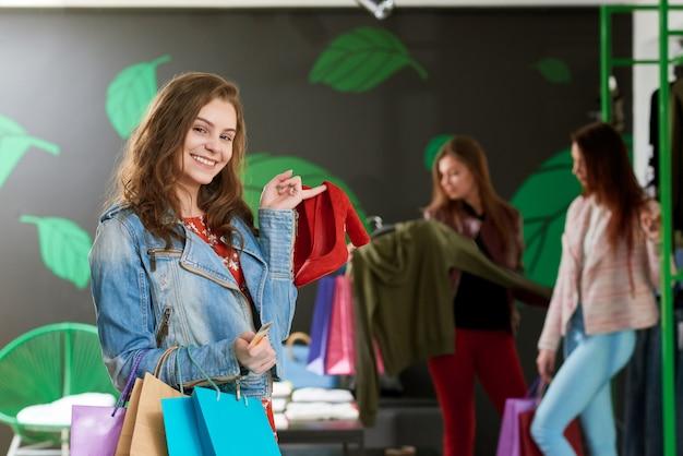 Positiva menina segurando par de sapatos vermelhos na loja