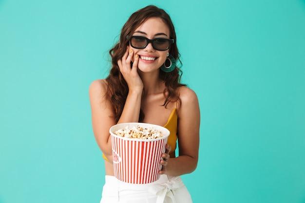 Positiva mulher bonita usando óculos, segurando o balde com pipoca e sorrindo para a câmera