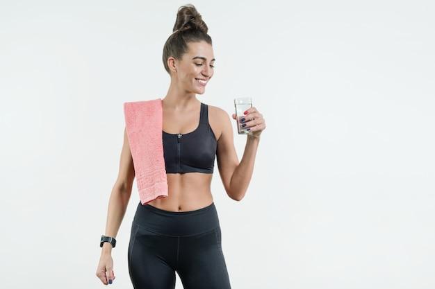 Positiva sorridente fitness mulher bebendo água