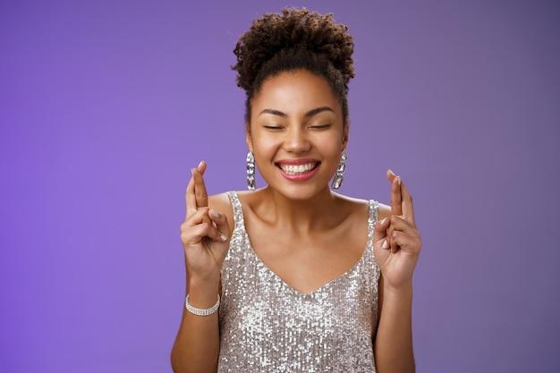 Positiva sorte encantadora jovem afro-americana comemorando aniversário fazendo desejo em elegante vestido prata fechar os olhos sorrindo otimista dedos cruzados sonho tornado realidade, fundo azul de pé.
