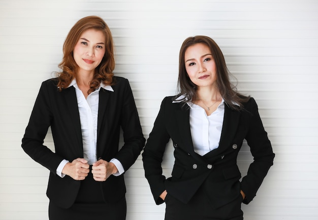 Positivas empresárias asiáticas com roupa formal, posando com autoconfiante, olhando para a câmera com um sorriso em pé perto de uma parede cinza. conceito para bons colegas e amigos no escritório de negócios.