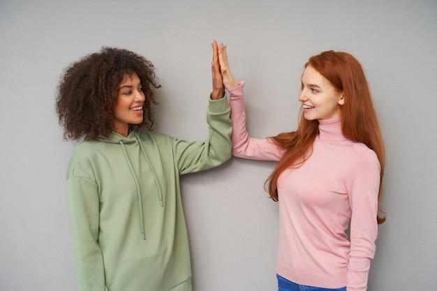Positivas lindas garotas olhando alegremente e sorrindo agradavelmente enquanto batem palmas umas das outras, estando de bom humor enquanto posam sobre uma parede cinza