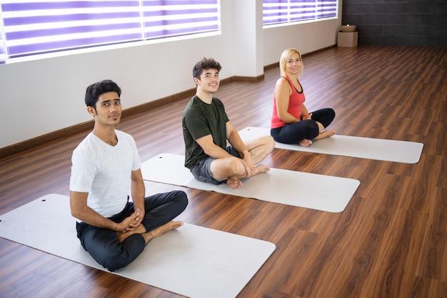 Positivas pessoas sentadas em esteiras na aula de ioga