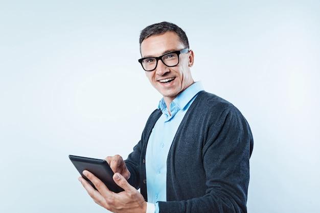 Positividade é a chave para o sucesso. tiro da cintura para cima de um cara maduro emocional ficando animado enquanto trabalhava em um computador tablet em segundo plano.