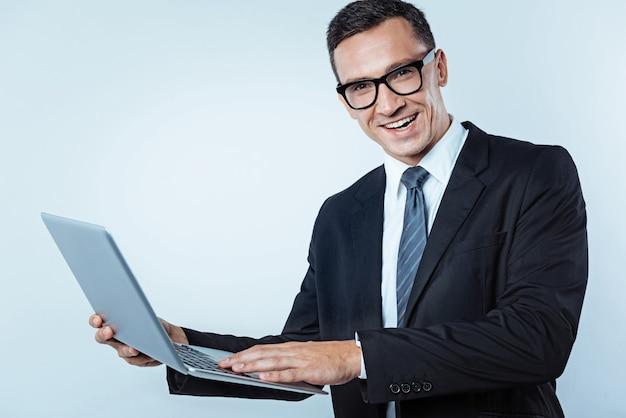 Positividade é a chave para o sucesso. tiro da cintura para cima de um empresário do sexo masculino usando óculos, segurando um laptop e sorrindo amplamente enquanto olha para a câmera.