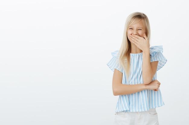 Positivo alegre adorável garota com cabelo loiro, cobrindo a boca enquanto ri