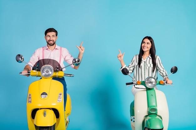 Positivo, alegre, duas pessoas, motociclistas, andam de scooter elétrica em alta velocidade, seguem o caminho para o ponto de viagem dedo indicador copyspace usar camisa rosa listrada isolada sobre parede de cor azul