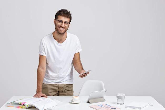 Positivo atraente homem não barbeado trabalha em reportagem