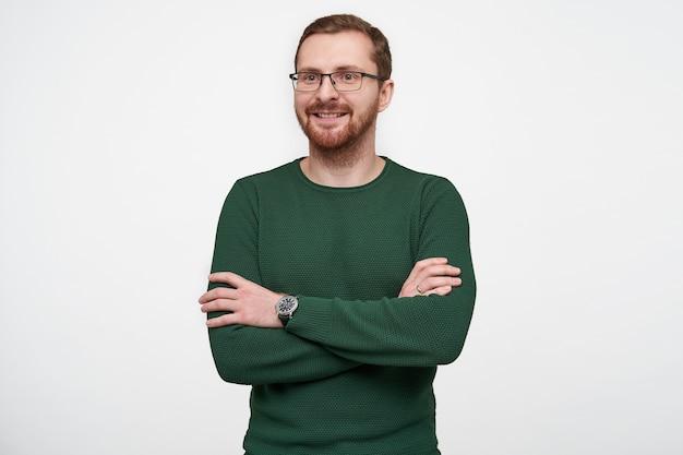 Positivo, bonito, jovem, barbudo, usando óculos, suéter verde, em pé, sorrindo ligeiramente e mantendo as mãos postas