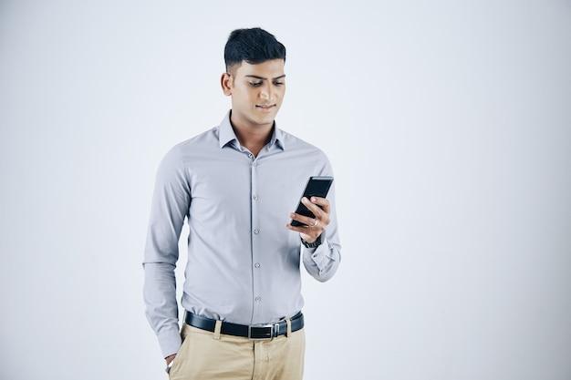 Positivo bonito jovem empresário indiano lendo mensagens de texto na tela do smartphone, isolado no branco