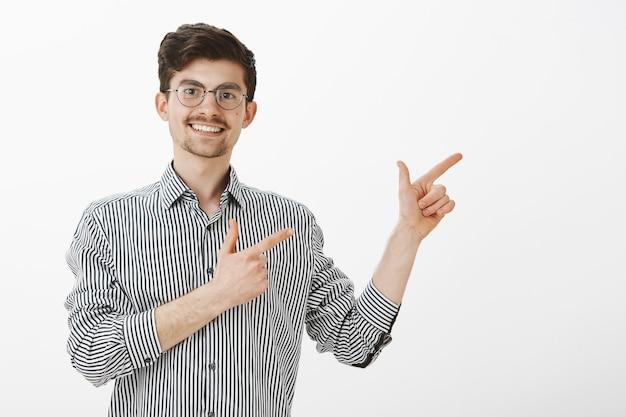 Positivo charmoso simpático homem com bigode e barba em elegantes óculos redondos, apontando para o canto superior direito com gestos de arma de dedo e sorrindo alegremente, estando de ótimo humor