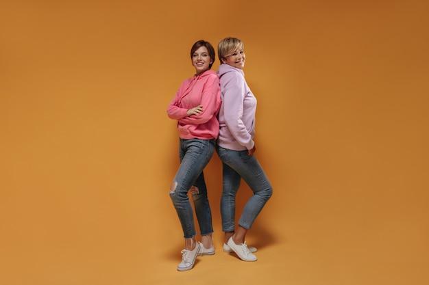 Positivo duas senhoras de cabelo curto com sorrisos adoráveis em moletom rosa da moda, jeans modernos e tênis legais, olhando para a câmera em fundo laranja.