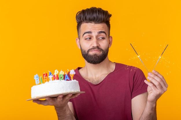 Positivo engraçado jovem asiático com um boné e uma vela acesa e um bolo nas mãos, posando em uma parede amarela. conceito de aniversário e aniversário.