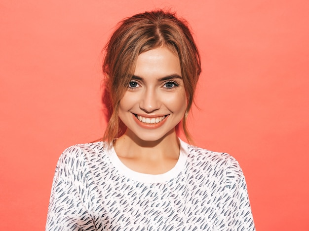 Positivo feminino sorrindo. engraçado modelo posando perto de parede rosa no estúdio
