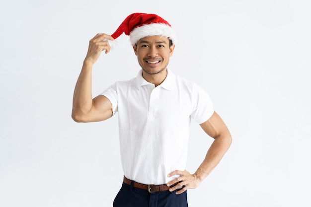 Positivo homem asiático tocando seu chapéu de papai noel