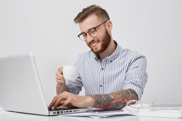 Positivo homem barbudo com penteado moderno, usa camisa formal, bebe cappuccino ou expresso,