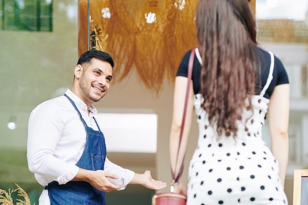 Positivo, jovem e bonito dono de um pequeno café fazendo um gesto de boas-vindas e convidando uma cliente a experimentar o novo manu