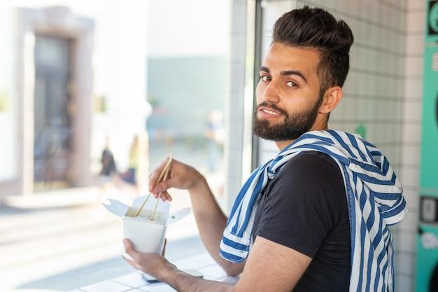 Positivo jovem elegante comendo macarrão chinês em um café durante uma pausa no trabalho. o conceito de descanso e lanche saudável.