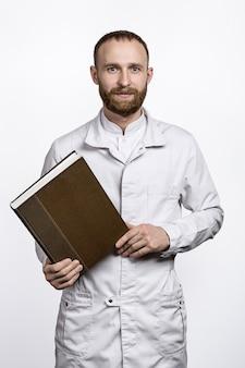 Positivo jovem médico com barba no jaleco branco. nas mãos de um grande livro.