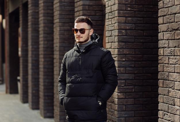 Positivo jovem sorridente em roupas elegantes, parado sozinho perto da parede de um prédio urbano e falando no celular