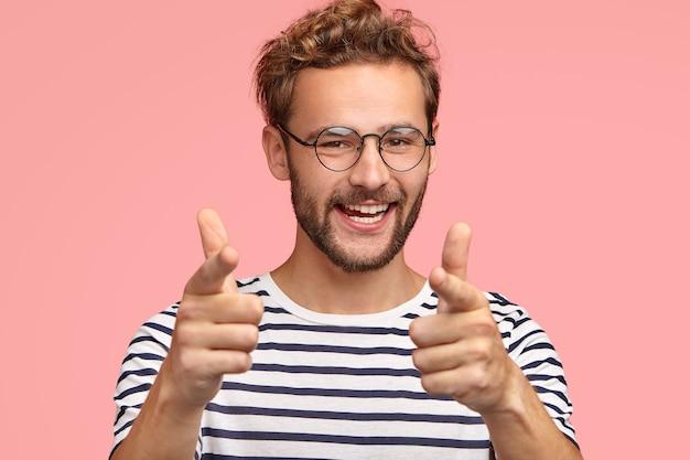Positivo masculino com a barba por fazer aponta para você, tem expressão alegre, cabelo encaracolado, eriçado, expressa sua escolha, usa roupas listradas, isoladas em parede rosa. homem faz gesto de arma com o dedo. você é meu tipo