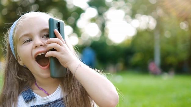Positivo menina criança conversando em seu telefone móvel no parque de verão. criança do sexo feminino falando no sellphone.