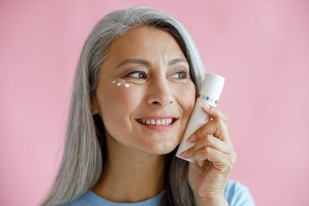 Positivo modelo asiático de meia idade com gotas de creme sob o olho segura a garrafa no fundo rosa no estúdio. estilo de vida de beleza madura