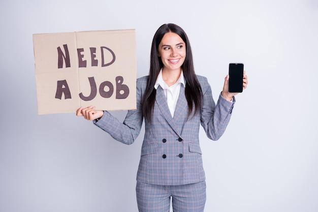 Positivo mulher agente banqueiro segurar smartphone papel cartão texto precisa de emprego navegar nas mídias sociais mercado de trabalho site usar calças xadrez xadrez blazer calças calças isoladas cor cinza fundo