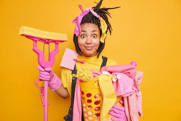 Positivo surpreso, dona de casa ocupada, lavando roupa e limpando a casa