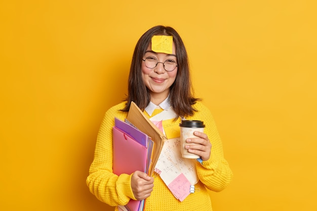Positivo trabalhador feminino asiático segura xícara descartável de café segura pastas tem adesivo com gráfico preso na testa tem pausa após aprendizagem de exame.