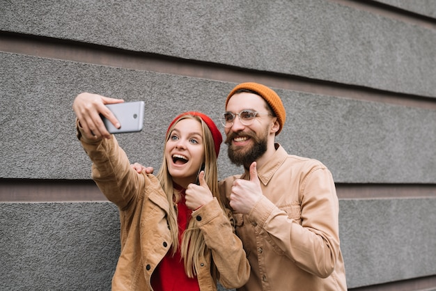 Positivos, sorridentes amigos hipster tirando selfies juntos, mostrando thump up