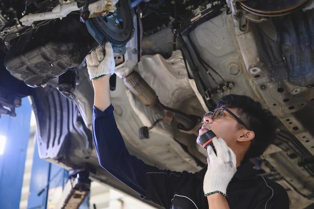 Posse mecânica masculina asiática e lanterna brilhante para examinar o carro sob o chassi