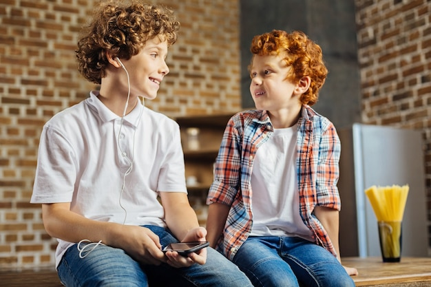 Posso tentar. garotinho ruivo bonito pedindo a seu irmão mais velho para ouvir a música tocando em fones de ouvido, enquanto ambos têm uma conversa agradável e estão sentados na cozinha.