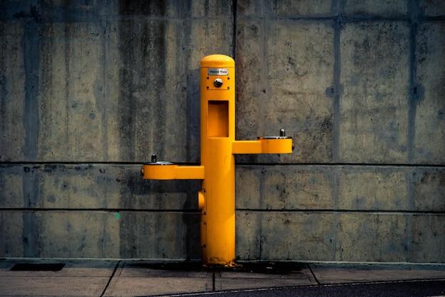 Post exterior de pedestal amarelo contra a parede