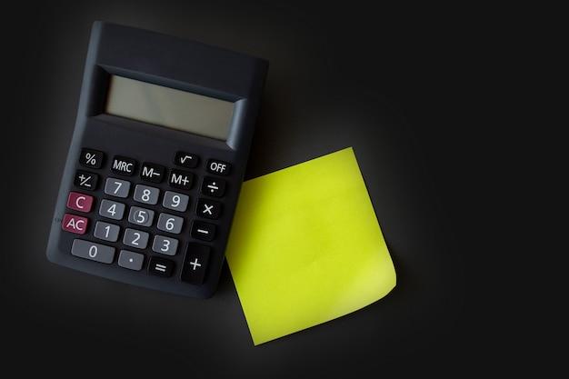 Post-it amarelo verde e calculadora preta sobre fundo preto cinza.