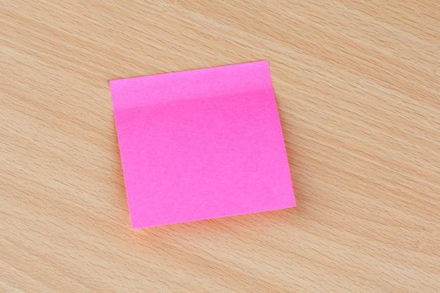 Post-it rosa preso numa superfície de madeira